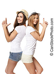 Two women friends having fun. Two happy girls in straw hats...