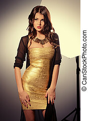 celebrity - Fashion shot of a gorgeous young woman in golden...