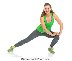 Smiling fitness young woman stretching