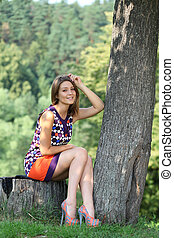 Young woman sitting in a summer park - Portrait of young...