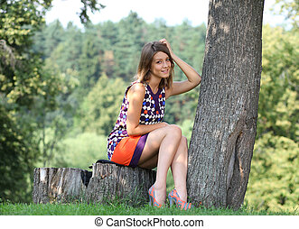 Young woman sitting in a summer park