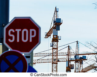 several cranes on construction site - at a construction site...