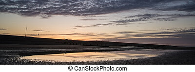 Beautiful sunrise panorama landscape reflected in pools on beach