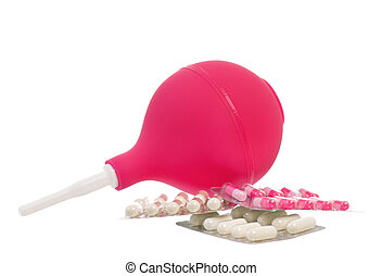Medical pink enema and colorful pills, isolated on white...