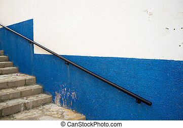 Banister on an old white and blue Mediterranean facade