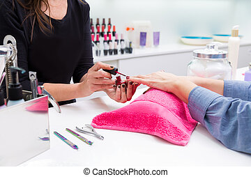 Nail saloon woman painting color nail polish in hands over...