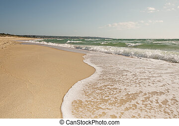 Breaking wave curve on sandy beach in motion with bubbles,...