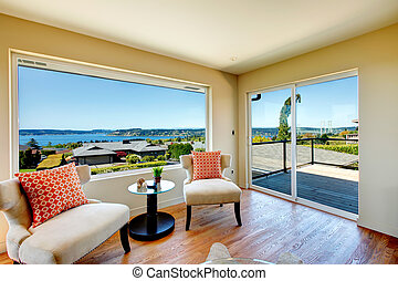 Ivory bright living room with hardwood floor, elegant chairs, decorated coffee table. Walkout deck opens an amazing landscape view