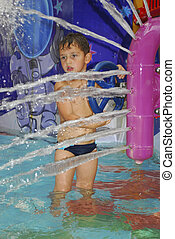 boy in the water park splashes water jet