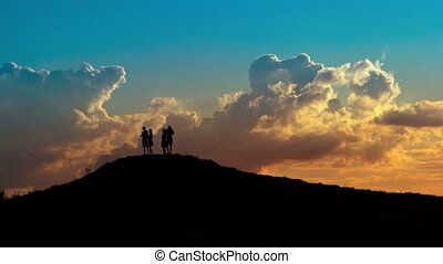 Silhouettes - People silhouettes on sunset sky background...
