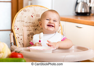 funny baby eating healthy food on kitchen