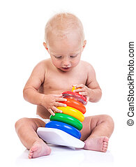 Cute little boy playing with pyramid toy on white