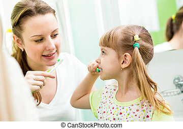 mother and child daughter brushing teeth in bathroom
