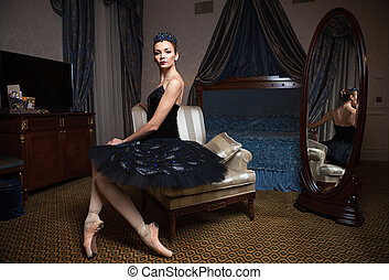 Ballerina in black tutu sitting in front of mirror -...