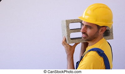 worker lifting heavy block - construction worker lifting...
