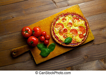 Pizza with vegetables on an old wooden board
