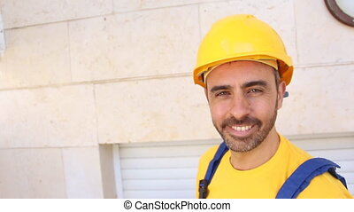 Construction man stand on a ladder - Handsome young bearded...