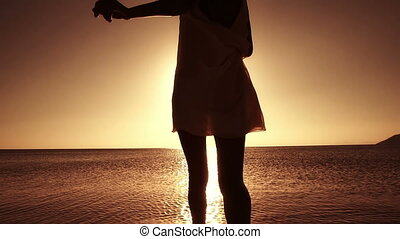 Woman Splashing Water - Sunset on the beach concepts. Super...