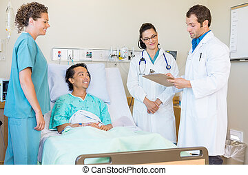 Young doctors discussing notes while nurse and patient...