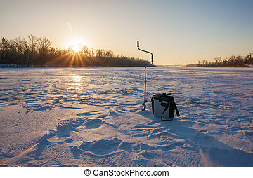 Ice fishing scene - sunrise on the river
