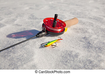Ice fishing rod with the lure on the snow
