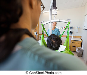 Nurse Smiling With Patient On Hydraulic Lift - Mid adult...