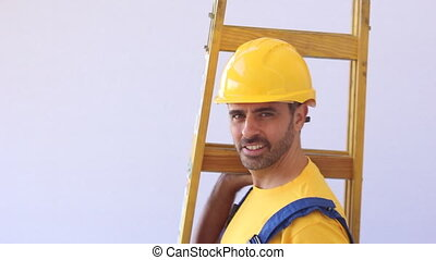 Workman in a hardhat carrying a ladder - Handsome young...
