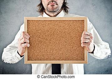 Businessman holding blank bulletin board