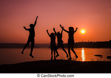 silhouette family jumping, sunset holiday