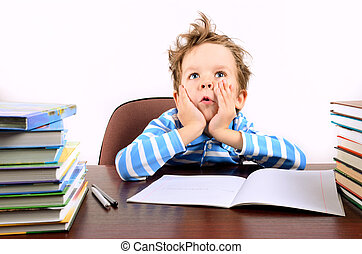 boy with tousled hair sitting at a desk. boy is 5 years....