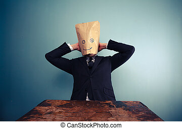 Businessman with bag over head relaxing