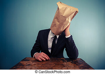 Sad businessman with bag over his head