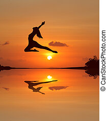 Silhouette of a beautiful ballet girl in sunset beach