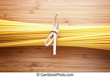 Bundle of Italian spaghetti pasta tied with string lying on...