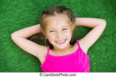 Little girl on green grass - Little smiling cute girl lying...