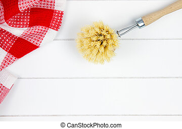 top-view of red checkered tea towel and dishwashing brush on...