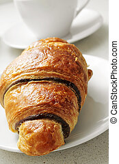 coffee and chocolate croissant - a chocolate croissant in a...