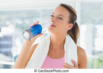 Woman with towel drinking water in gym
