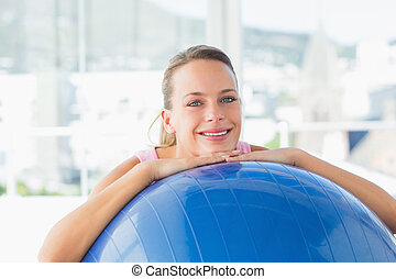 Smiling fit woman with exercise ball at gym - Portrait of a...