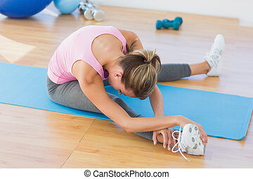 Sporty woman stretching hand to leg in fitness studio