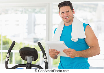 Smiling trainer with clipboard in gym - Portrait of a...
