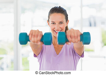 Smiling young woman lifting dumbbell weights