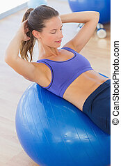 Fit woman exercising on fitness bal - High angle view of a...
