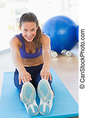 Sporty young woman stretching hands to legs in fitness studio