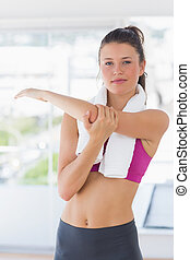 Portrait of a sporty woman stretching hand at yoga class -...