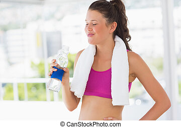 Fit woman with towel drinking water in gym