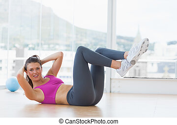 Young woman doing pilate exercises in fitness studio - Full...