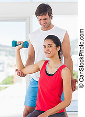 Instructor assisting woman with dumbbell weight