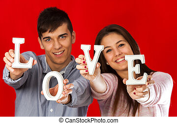 Couple playing with love block letters - Close up portrait...