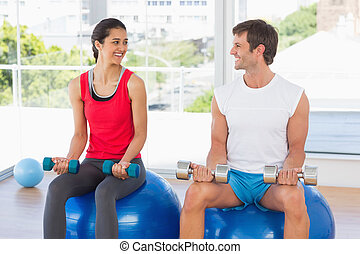 Happy man and woman lifting dumbbell weights while sitting on fitness balls in a bright gym